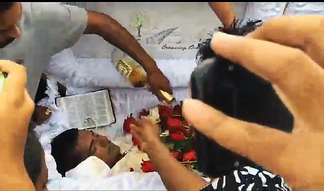 COGNAC SEND-OFF: This screen grab, taken from video images posted to social media, shows a mourner pouring Hennessy cognac on the body of Phillip Basant, brother in law of murdered auto dealer Sheron Sukhdeo. Basant, who himself was gunned down, was cremated on Tuesday.