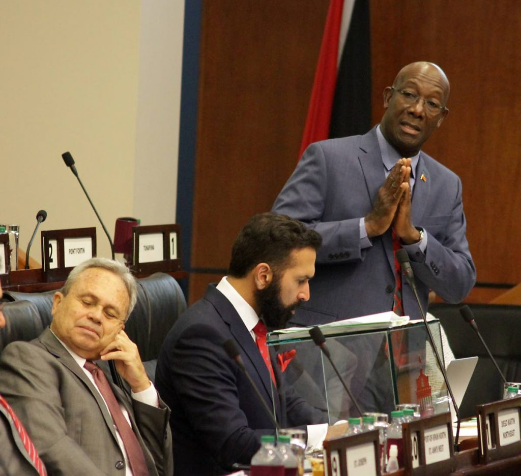 PROUD PM: Prime Minister Dr Keith Rowley addresses the House of Representatives yesterday during debate on the mid-year budget review. Also in photo are AG Faris Al-Rawi, centre, and Finance Minister Colm Imbert.