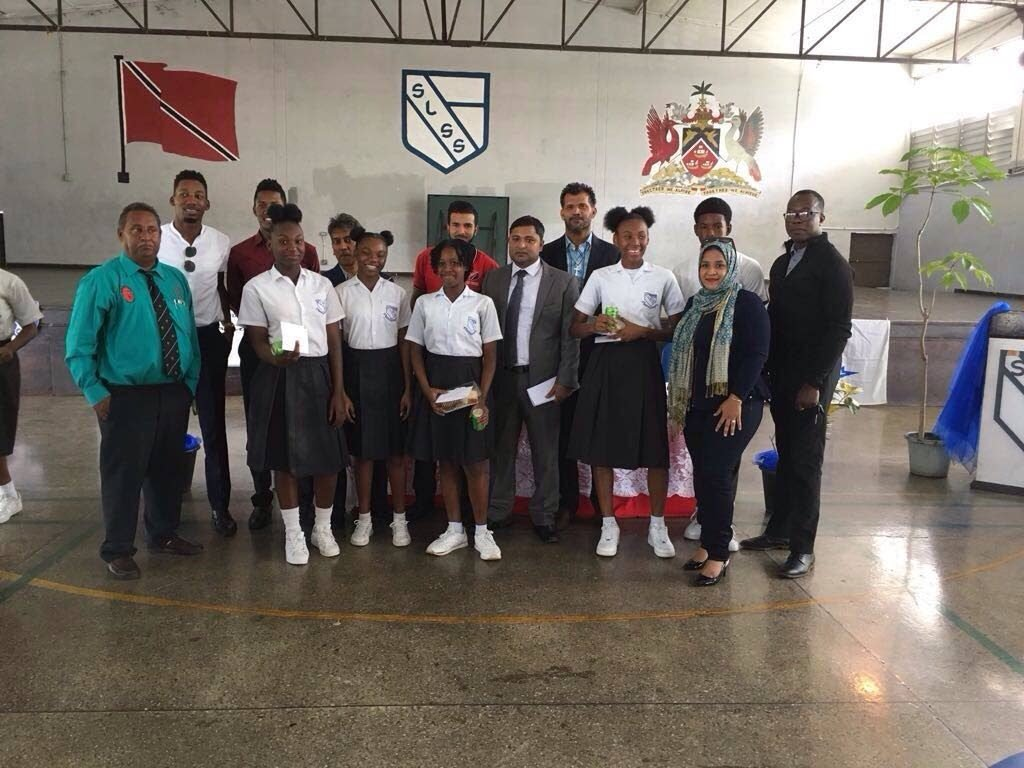 SUCCESS WORKSHOP: Former national and WI U15 cricketer Zaheer Ali,front row centre,  poses with national cricketers and students of the Success Laventille Secondary School yesterday  during a workshop held by Zaheer Ali Foundation at the school hall.