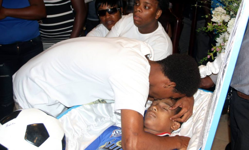 Daniel Simmons hugs his brother of Noah one last time at his funeral yesterday at Gudies Funeral Home in San Fernando. Noah was gunned down on his 16th birthday Tuesday.