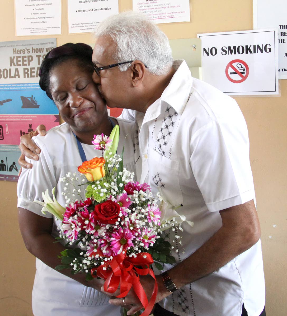 DON'T BLUSH: Nurse Jacqueline Jones-Flament receives flowers from Minister of Health Terrence Deyalsingh at the Port of Spain General Hospital on Mother's Day yesterday.
