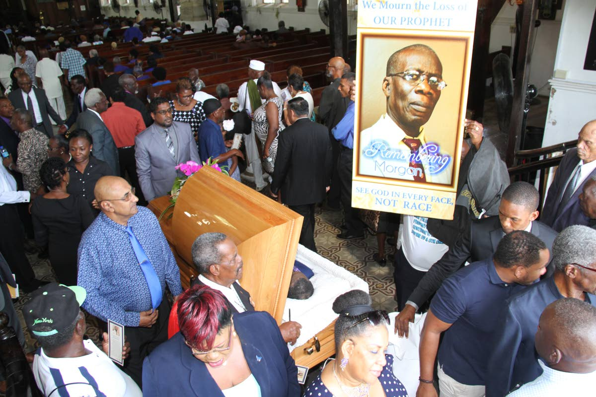 RIP: A large portrait of Dr Morgan Job is held high by a man at his funeral held at the Holy Trinity Cathedral in Port of Spain yesterday as hundreds file pass his casket.