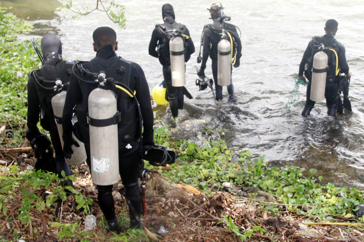 OFF TO SEARCH: Divers from the Coast Guard enter a pond in Ste Madeleine yesterday to search for a child. They left empty handed.