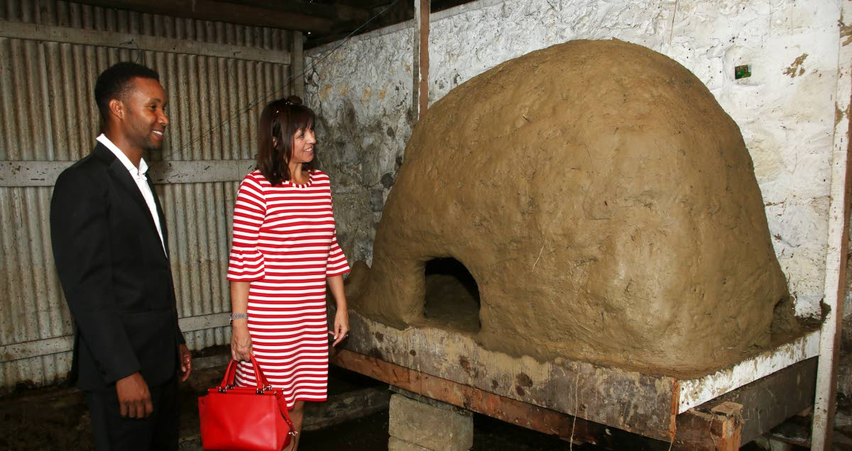 YESTERYEAR'S OVEN: Merikin Prince of Moruga Eric Lewis shows Deputy British High Commissioner Caroline Alcock a refurbished earthen oven which was used to roast cocoa, at the Cocoa Museum in Moruga on Saturday.