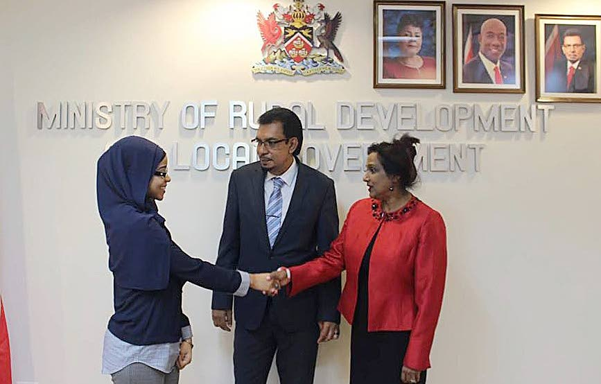 WELCOME: Nafisah Nakhid is greeted by Minister of Rural Development and Local Government Kazim Hosein, and permanent secretary Stara Ramlogan at the ministry's head office yesterday.
