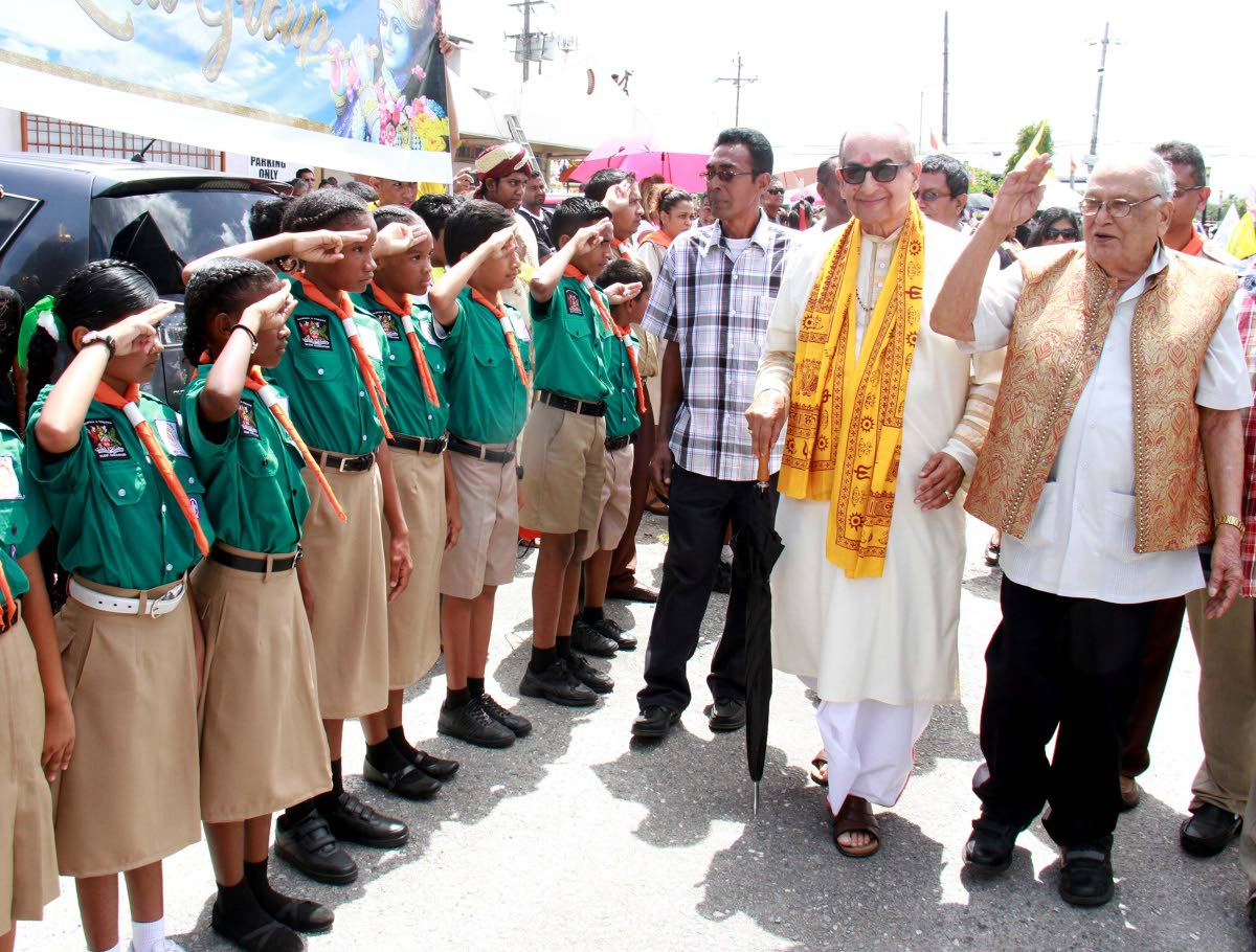 SALUTE: Secretary general of the Sanatan Dharma Maha Sabha Satnarayan Maharaj (right)  and Dharmacharya Pundit Utam Maharaj (second from right) are saluted by scouts at Indian Arrival Day celebrations at the Parvati Girls' Hindu College in Debe yesterday.