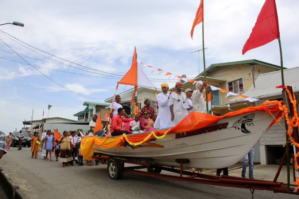 WE'VE ARRIVED: Opposition Leader Kamla Persad-Bissessar sits in a boat, which depicts the Fatel Razack on which East Indian indentured labourers came to TT from India, at Indian Arrival Day celebrations at Bonasse Village, Cedros yesterday.