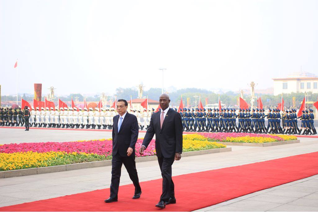 ON CHINESE SOIL: Prime Minister Dr Keith Rowley and Premier of the State Council of the People Republic of China leave after inspecting a guard of honour shortly after Rowley arrived in Beijing to kick off a state visit to that country. PHOTO COURTESY OFFICE OF THE PRIME MINISTER