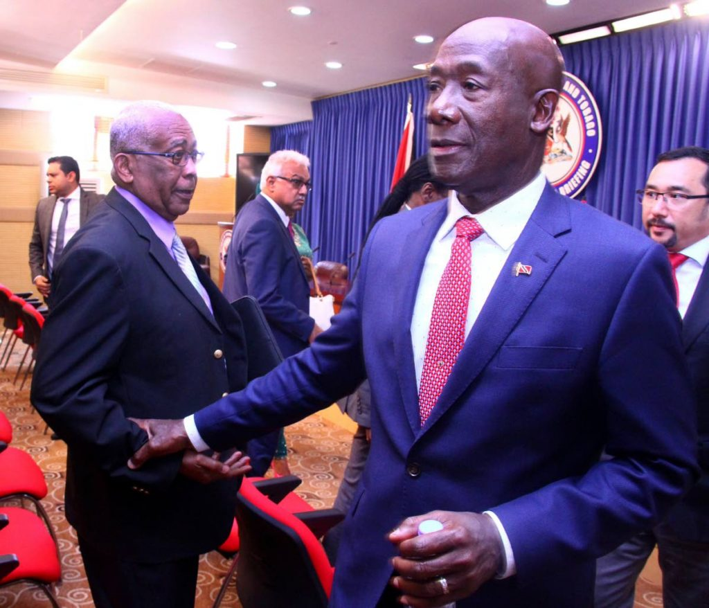 PM Dr Keith Rowley greets Anthony Garcia, Education Minister, after addressing members of the media, about his official visit to China and Australia, Diplomatic Centre, St Ann's. Tuesday, May 30.