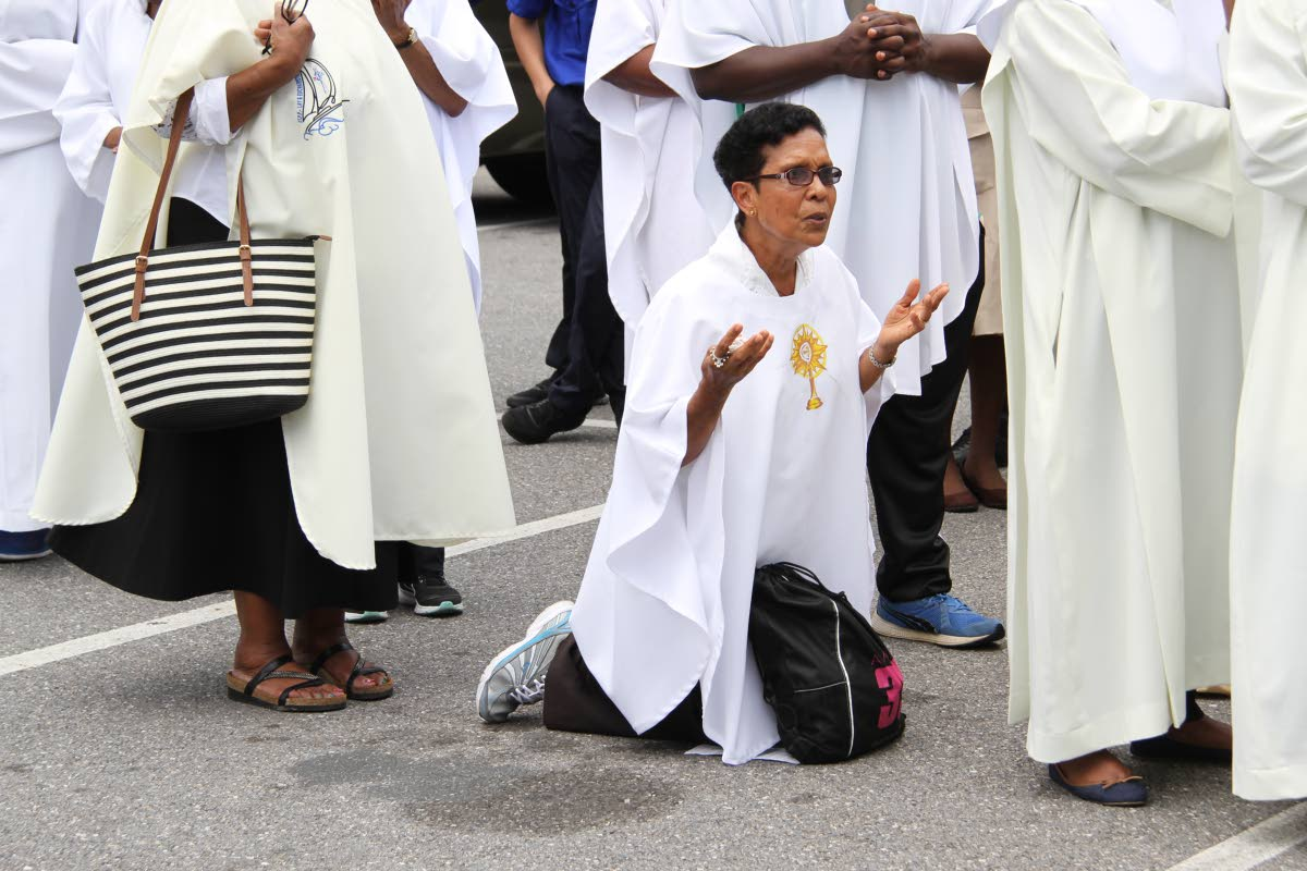 PRAYING: A woman kneels ouside the Cathedral of the Immaculate Conception as thousands celebrated Corpus Christi, yesterday. PHOTO BY SUREASH CHOLAI