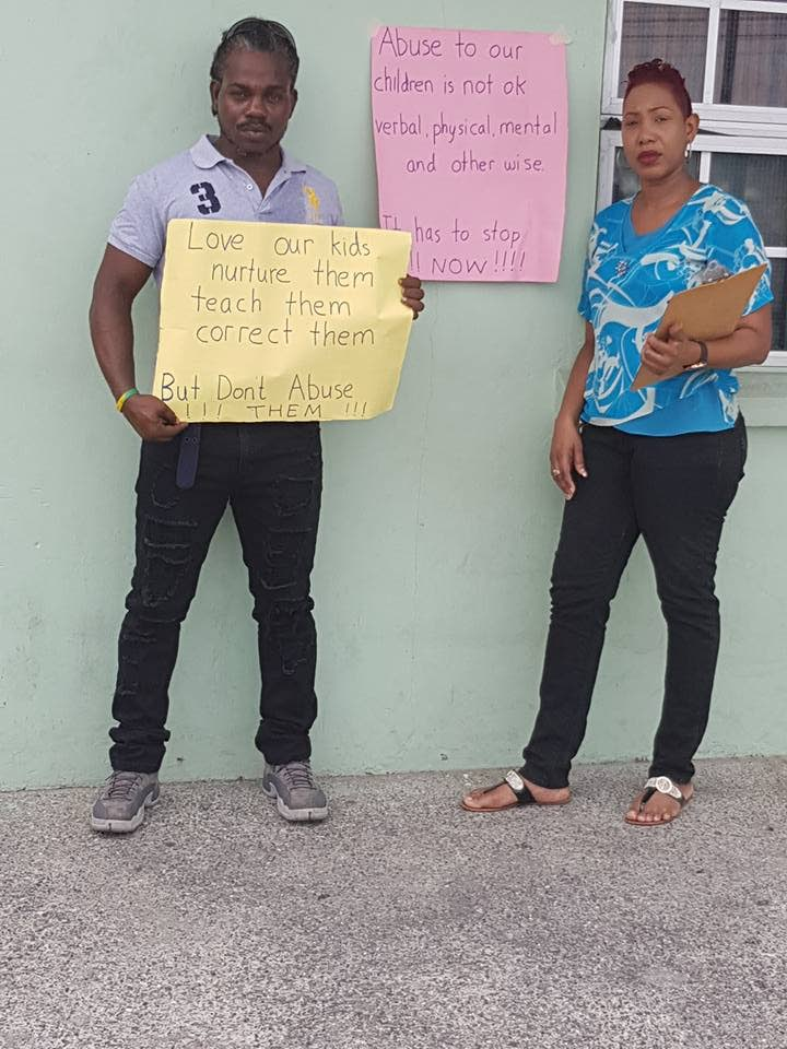Dale Barclay, left and Jemilla Bailey staged a protest outside the Tranquility Government Primary School yesterday after a male teacher at the school allegedly assaulted Bailey's 9-year-old son last week