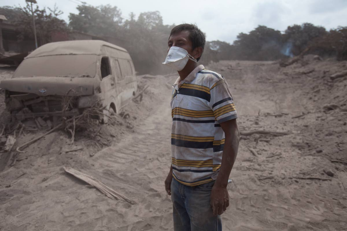 DESOLATE: A man waits for a rescue team in the  ash-covered village of San Miguel Los Lotes.