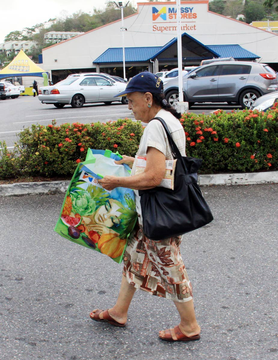 BAG IN HAND: A woman walks with her reusable bag which she collected on Tuesday at Massy Stores in Maraval. PHOTO BY ANGELO MARCELLE