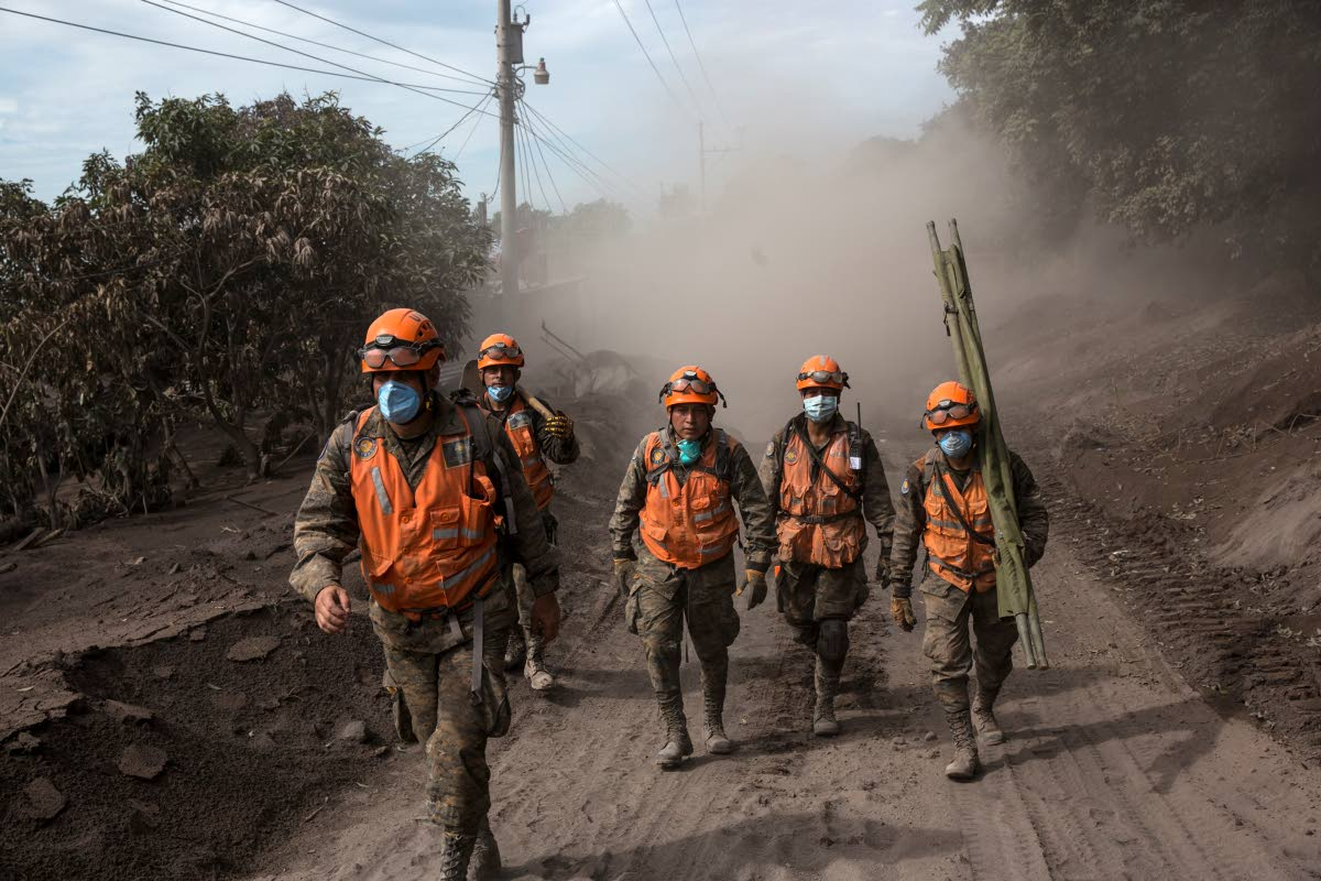 Rescue workers walk near the Volcan de Fuego in El Rodeo, Guatemala yesterday. AP PHOTO