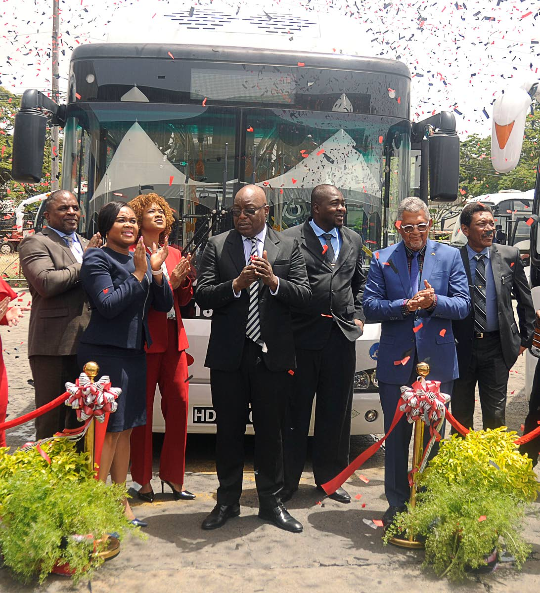 Chief Secretary Kelvin Charles, fourth from left, applauds at the commissioning of 15 new buses for Tobago on Tuesday along with, from left, Finance Secretary Joel Jack,MP for Tobago West, Sports Minister Shamfa Cudjoe, MP for Tobago East, Minister of State in the Office of the Prime Minister -Ayanna Webster-Roy, Public Utilities Secretary Clarence Jacob and PTSC Chairman Edwin Gooding. The commissioning and blessing ceremony of the new PTSC buses was held at the bus depot, Old Government Farm Road, Shaw Park.  THA photo