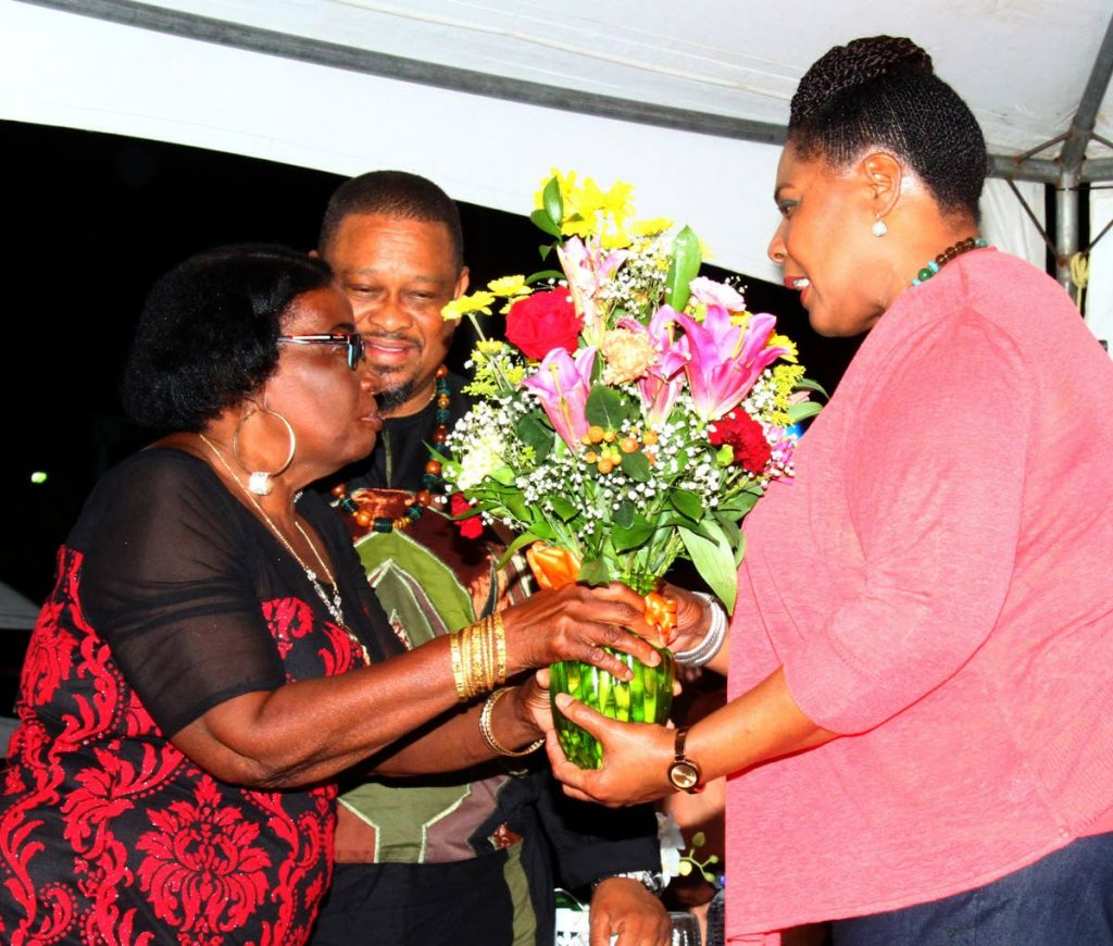 President Paula-Mae Weekes receives a boutique of flowers from Joycelyn Le Blanc, president of Sea Lots Village Council at the launch of i95.5FM's 2018 Laventille Nights series at the Sea Lots Basketball Court, Port of Spain, on Friday night.