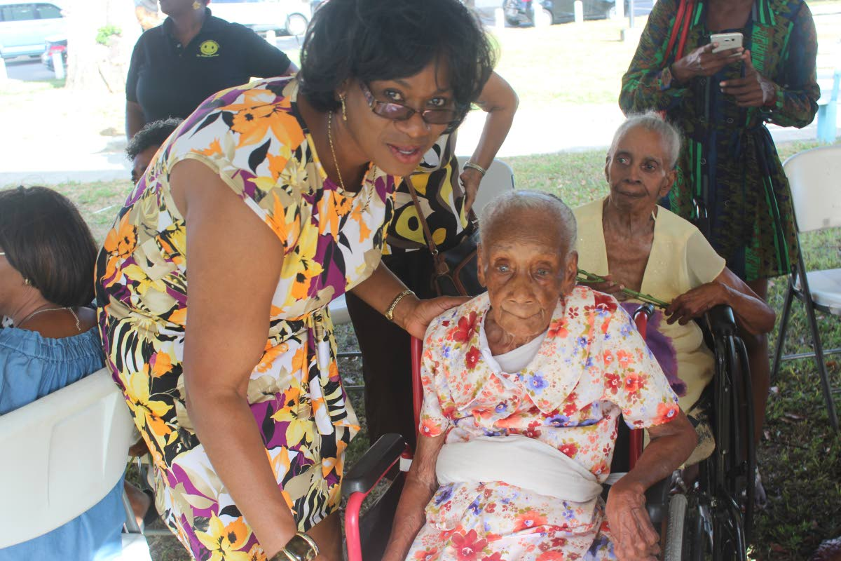 Deputy Commissioner of Police Earla Christopher greets 102-year-old Esther Waldron at Saturday's public discussion on elder abuse hosted by the police service Witness and Victim Support Unit. Photo: Enrique Asson