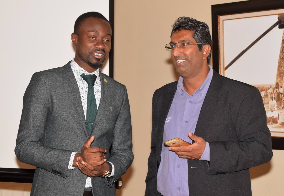 THA Minority representative Farley Augustine, left,  chats with Economist Dr Roger Hosein, Senior Lecturer at UWI, St Augustine at the environment symposium last Thursday at the Mt Irvine Bay Resort.