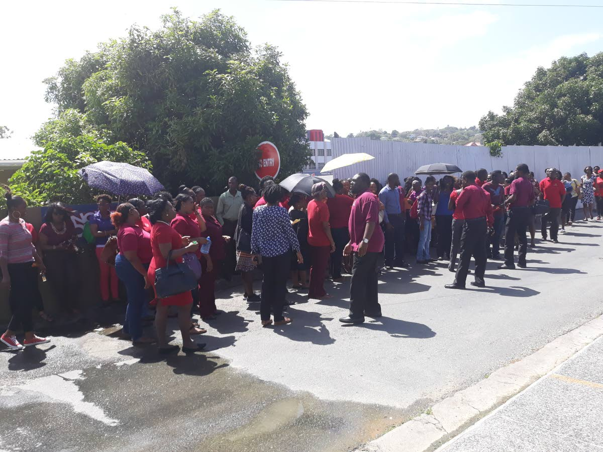 Teachers gather outside theDivision of Education at Dutch For Street, Scarborough on Monday to protest lack of action on promoting them from Assistant Teacher 1 positions to Teacher 1.