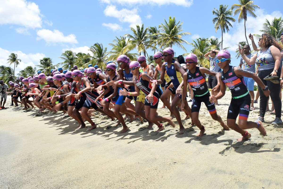 Children run for the water at the start of the 375m swim portion of the 13-15 age group Youth Triathlon at the 14th Annual Massy Rainbow Cup at Courland Bay Heritage Park, Tobago, on Saturday.