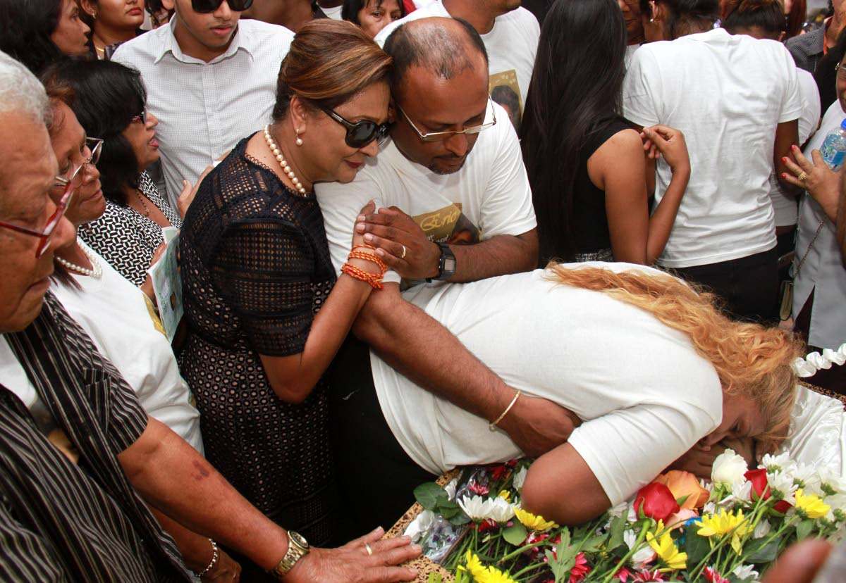 Opposition Leader Kamla Persad Bissessar hugs Vishnu Ganesh while his wife Waheeda leans over the coffin with their son Eric Ganesh during his funeral service, which took place at St. Charles Village, Princes Town.  PHOTO BY ANIL RAMPERSAD.