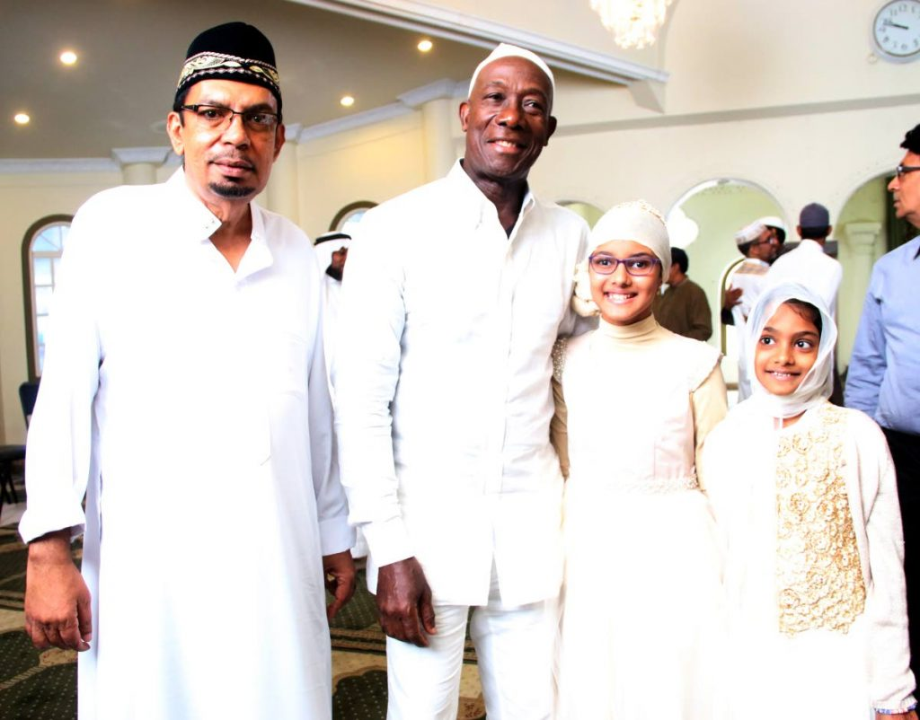 Celebrating Eid: Local Government Minister Kazim Hosein, left, and Prime Minister Dr Keith Rowley  pose for a photo with Asiya Baksh, second from right, and her sister Nayyara Baksh yesterday at the  Mucurapo Street Mosque in San Fernando. PHOTO BY ANSEL JEBODH