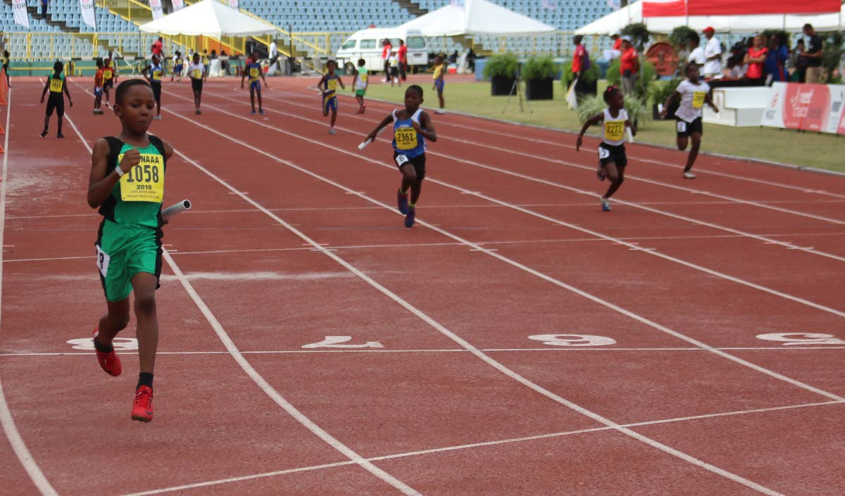 A Cougars athlete, left, sprints to gold in the Under-11 4x100m mixed relay event at the NGC NAAA National Juvenile Championships at the Hasely Crawford Stadium, Mucurapo, Saturday.