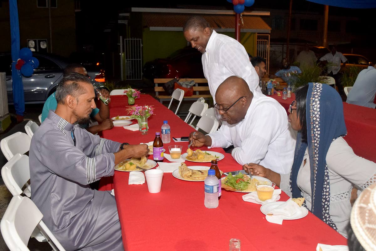 Finance Secretary Joel Jack, standing, joins Chief Secretary, Kelvin Charles, centre right,  and his wife Catherine Anthony-Charles as share an Eid-ul-Fitr celebratory meal with  Kameal Ali, coordinator and administrator for Majid al Tabwah in Lowlands on Thursday night.