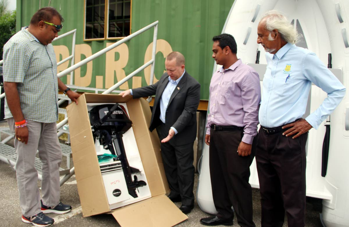 BRAND NEW: US Embassy deputy Chief of Mission John McIntyre, centre, inspects new boat engines donated by the Embassy to the Penal/Debe Regional Corporation yesterday. Also in photo are Alderman Purinshottan Singh, left, Vedesh Lall and corporation chairman Dr Allan Sammy, right. PHOTO BY ANSEL JEBODH