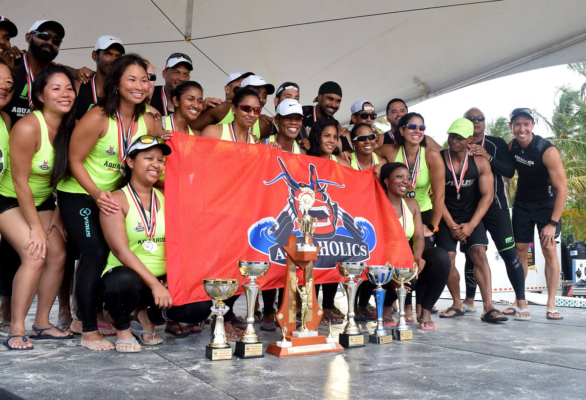 DOMINANT: Aquaholics show off their trophies at the awards ceremony of the Pigeon Point Heritage Park Annual Dragon Boat Festival, at Pigeon Point Beach, Tobago, Sunday.