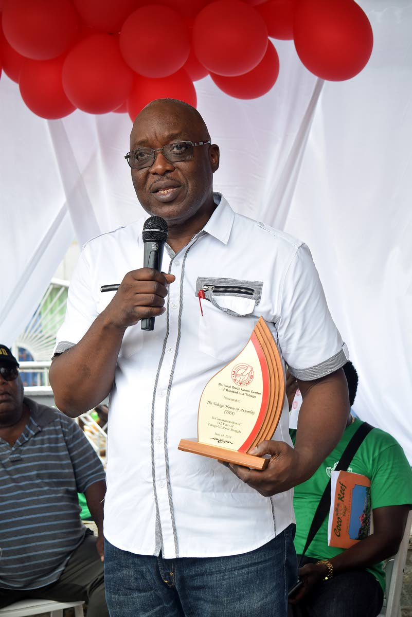 Chief Secretary Kelvin Charles holds an award presented to him in commemoration of the historic first labour march and rally held in Tobago to celebrate Labour Day, at James Park on Tuesday.