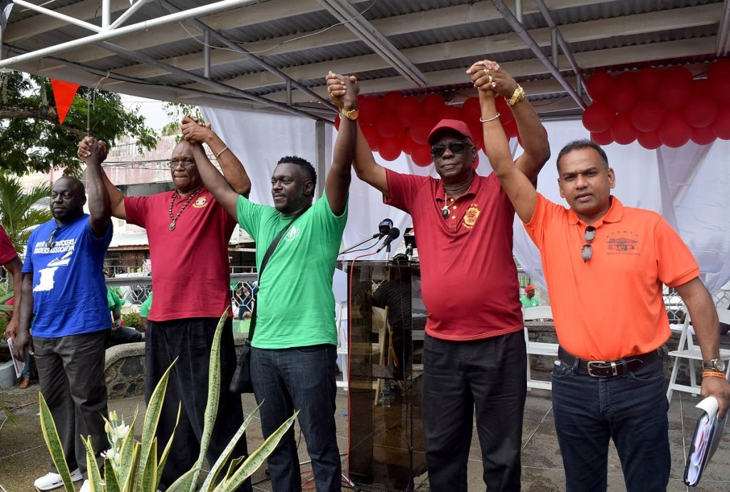 Solidarity: Trade union leaders raise clasped hands in a show of solidarity at Tuesday's Labour Day rally at James park, Scarborough. From left are Horace Amede, President of the Inter-isle Truckers and Traders Association; Michael Annisette, President of the Seamen and Waterfront Workers Trade Union (SWWTU); Watson Duke, President of Public Services Association (PSA) and the National Trade Union centre (NATUC) Watson Duke; James Lambert, President General of the National Union of Government and Federated Workers (NUGFW) and Nirvan Maharaj, President General of All Trinidad General Workers Trade Union (ATGWTU.
