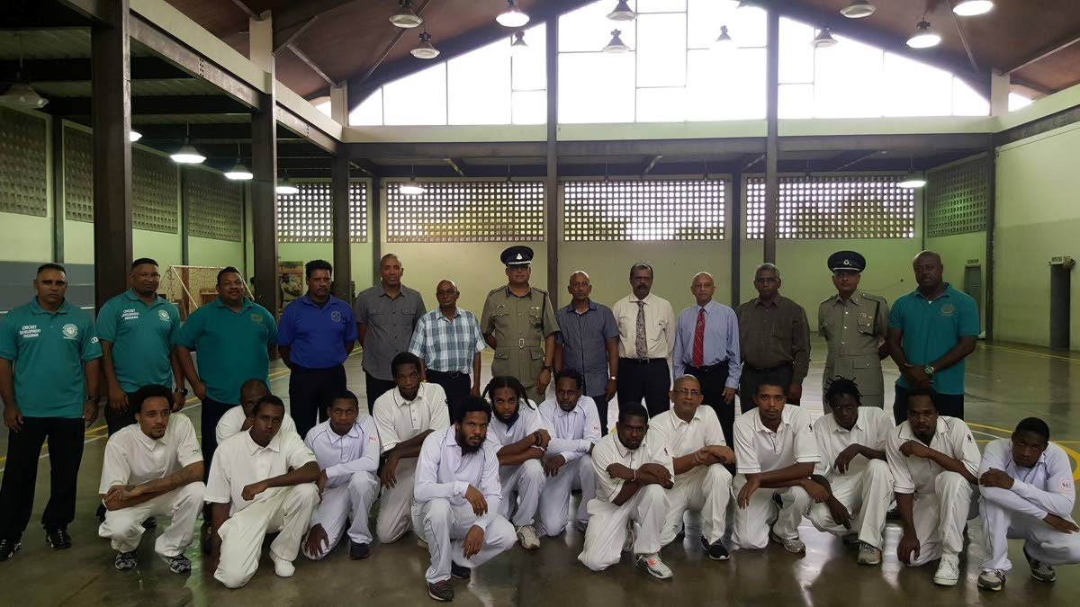Prison officials, TT cricket officials and members of the inmate cricket team pose at the launch of the Inmate Cricket Development Programme at the Maximum Security Prison in Arouca on Monday.