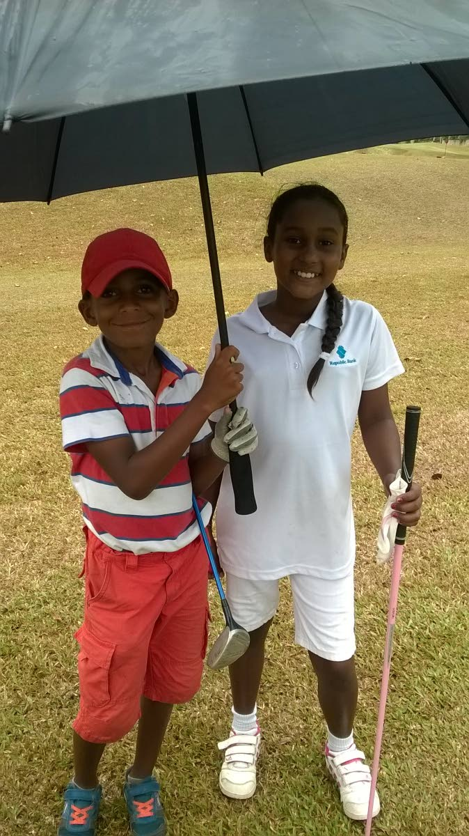 A supporter shelters Faatimah Emamalie in the Republic Bank 2015 Junior Golf Tournament at St Andrews Golf Club, Moka, Maraval. PHOTO COURTESY ALICIA EMAMALIE
