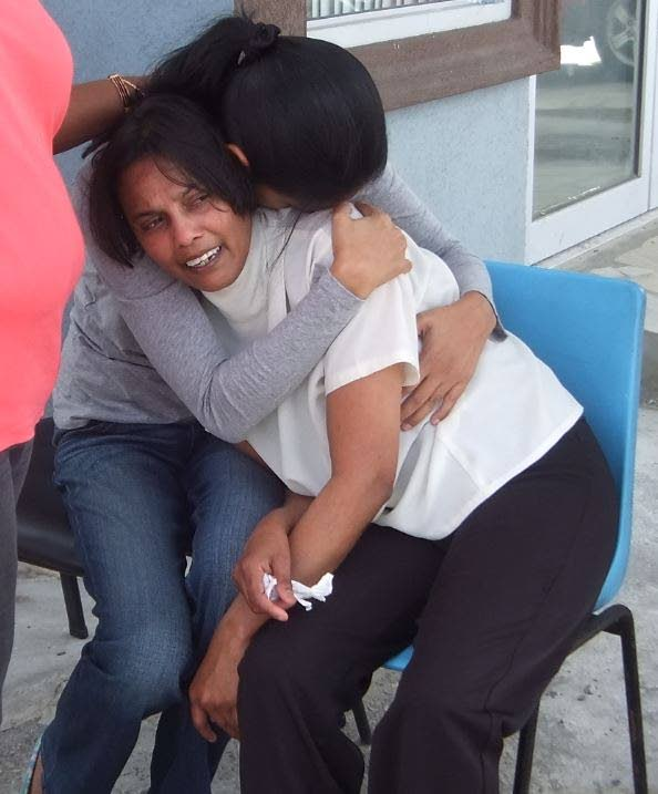 SORROW AND SHOCK: Attorney Mary Ramcharitar, right,  is consoled outside her Chaguanas  office yesterday after she  discovered the body of her secretary Nicole Debideen whose throat was slit. PHOTO BY STACY MOORE
