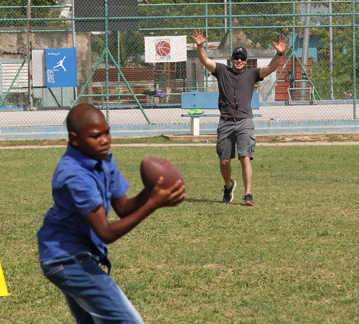 Good catch: A boy catches the ball in a game of American football with Alex Kenna of the Civil Affairs Unit, US Embassy at Enterprise Recreation Ground, Enterprise.