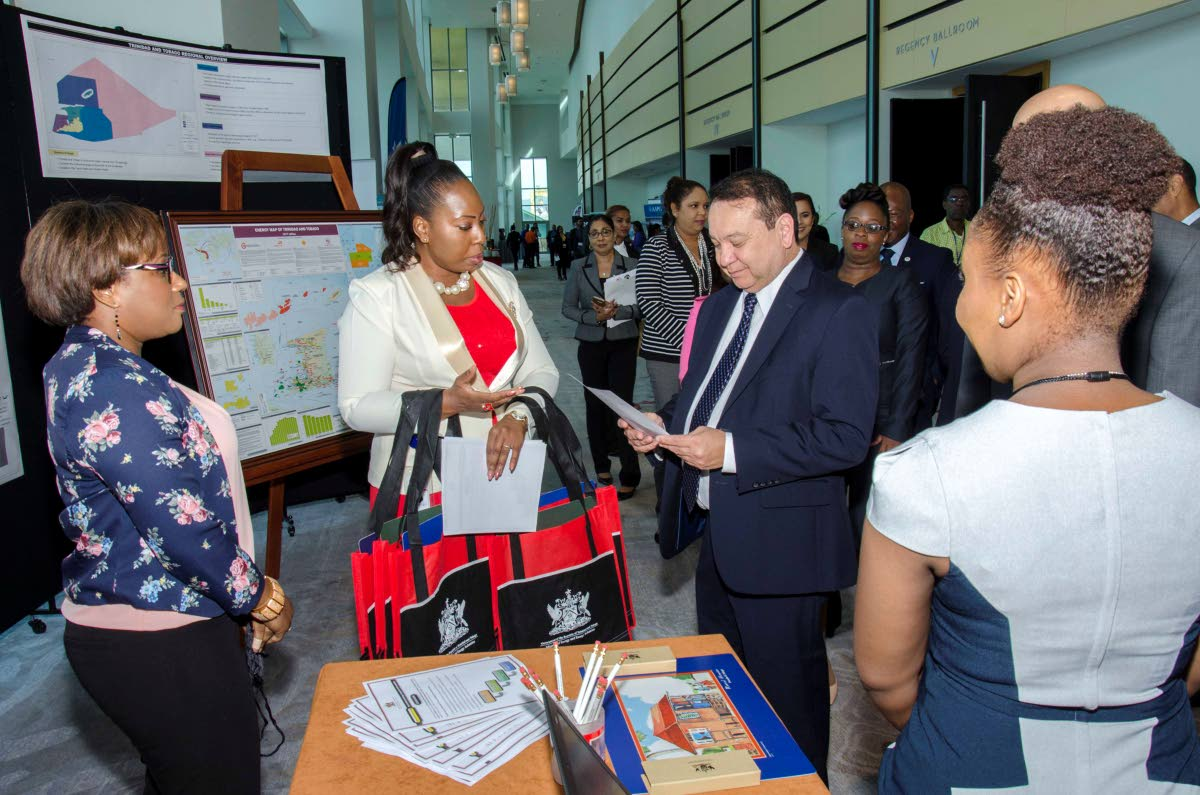 Energy Minister Franklin Khan browses through some of the brochures on display by energy companies at yesterday's 2018 Energy Resources conference and exhibition at the Hyatt in Port of Spain.