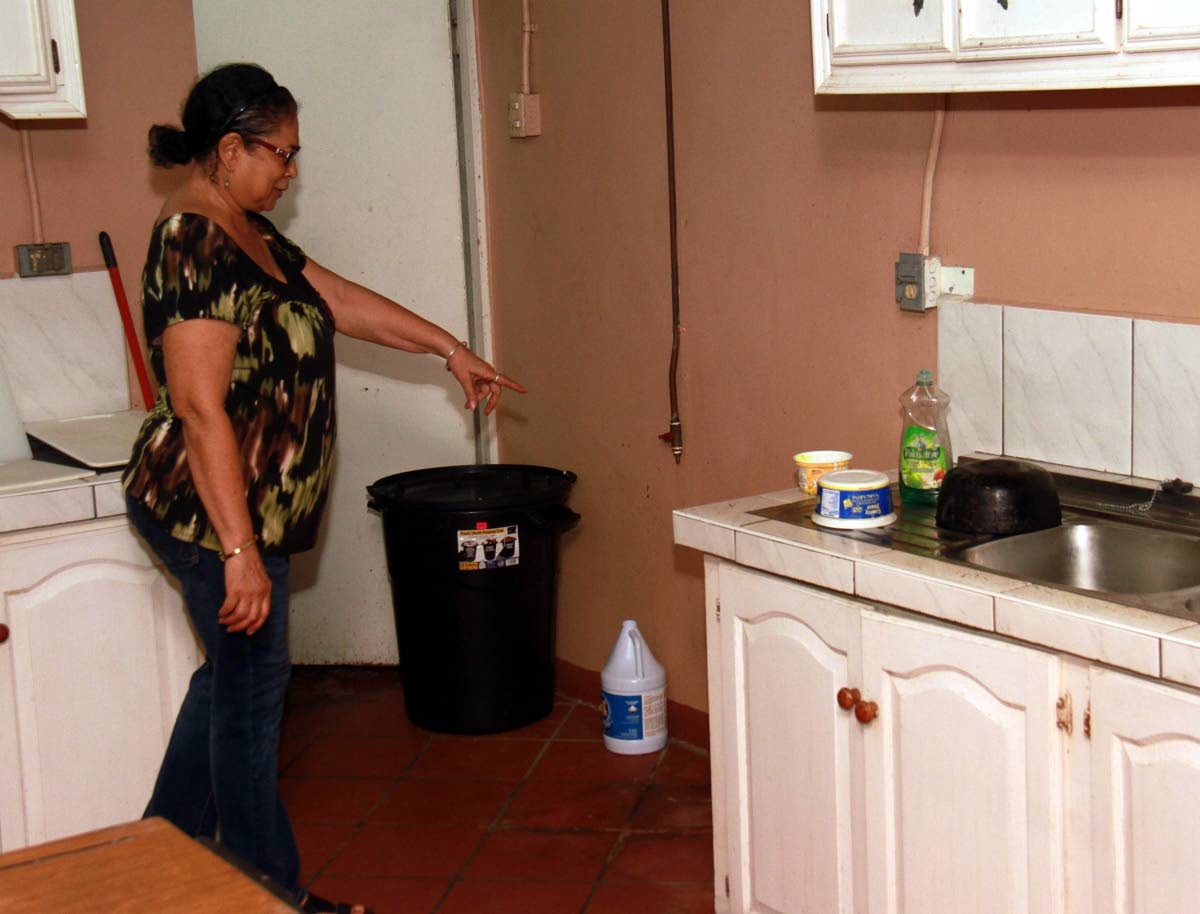 GONE: Chief cook Joan Lee Chong points to the space left after a stove was stolen from the soup kitchen of the Holy Cross  RC Church in Princes Town. PHOTO BY ANIL RAMPERSAD.