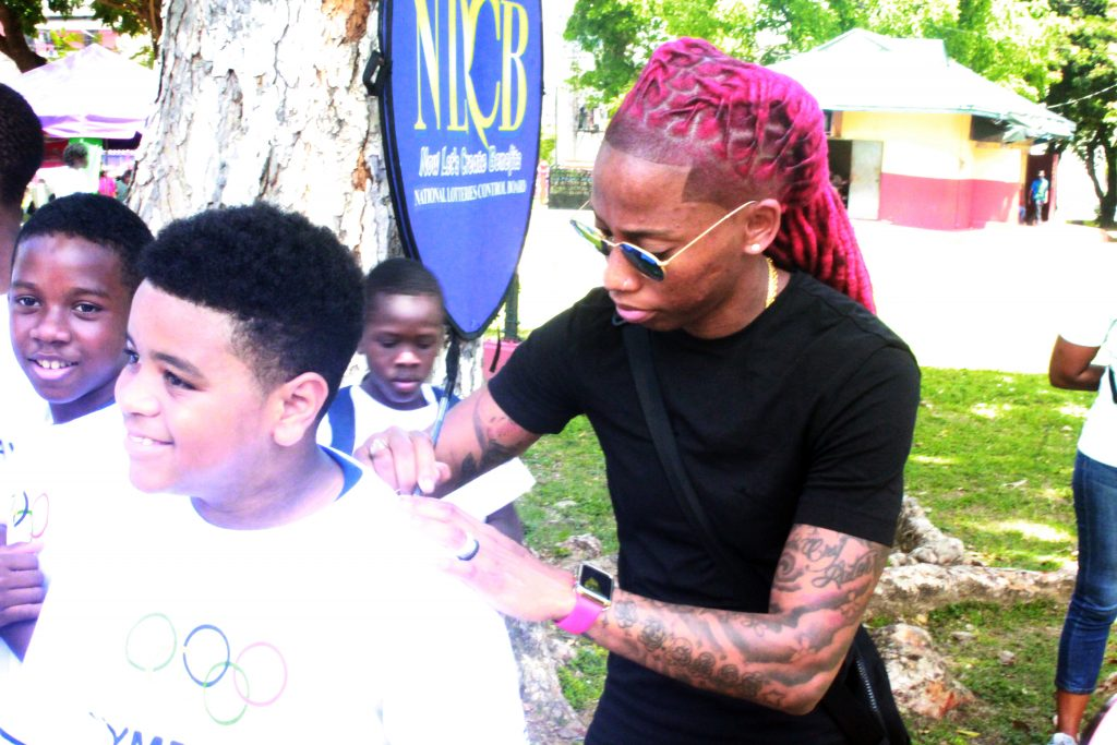 Commonwealth gold medallist and Olympic finalist Michelle Lee Ahye signs an autograph for a boy at Olympic Day, Woodford Square, Port of Spain yesterday. PHOTO BY ERIQUE ASSON