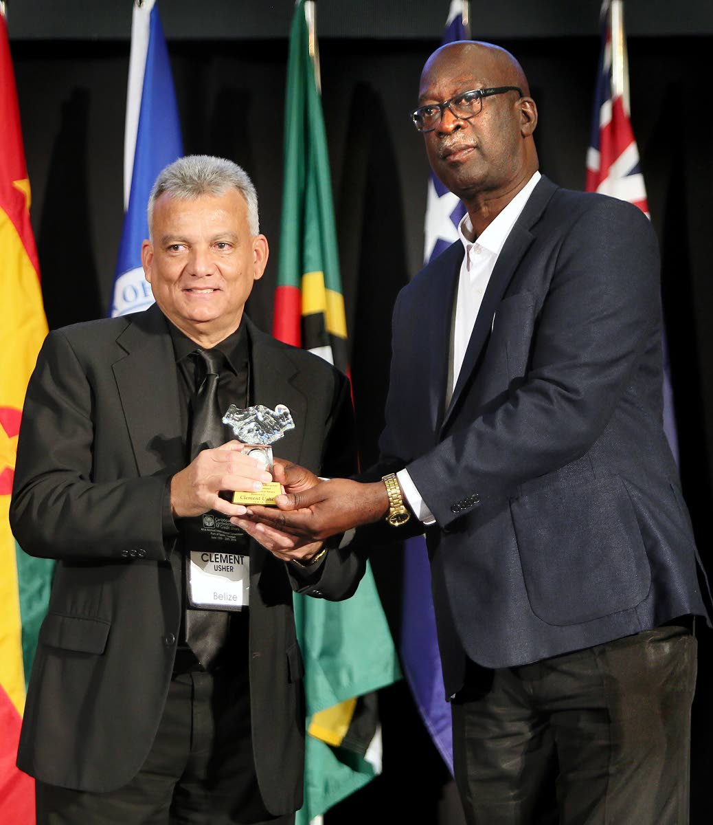 Joseph Remy, vice president of the Caribbean Confederation of Credit Unions (CCCU), right, presents a long-service award to Clement Usher, at the 61st annual international convention of the CCCU at the Hyatt Regency, Port of Spain, on Saturday.