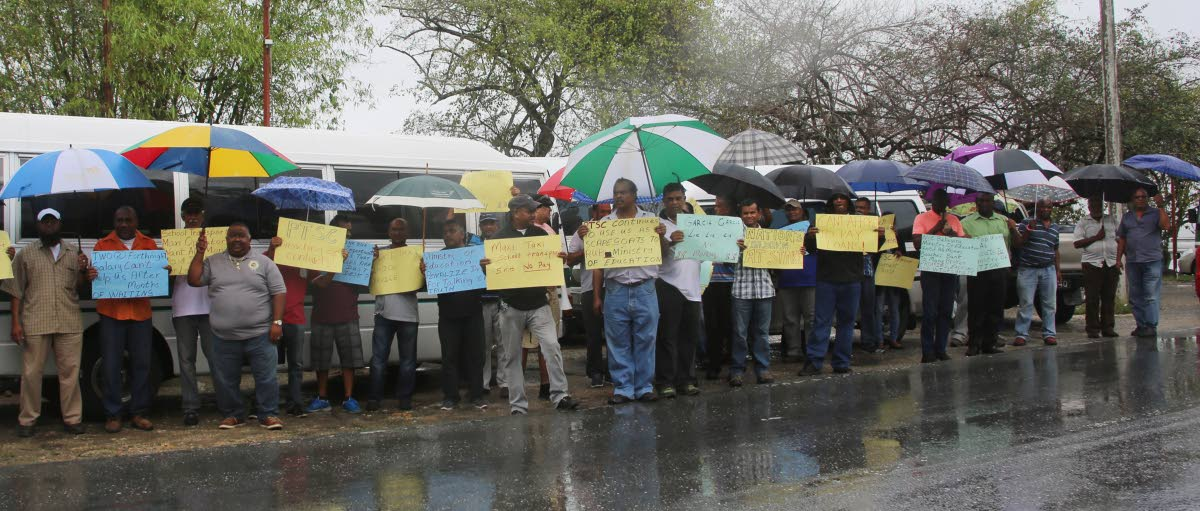 PROTEST: Despite heavy rainfall drivers of the Maxi Taxi  Concessionaires Association yesterday protested  with placards, oposite PTSC on Lady Hailes Avenue , San Fernando. PHOTO BY VASHTI SINGH