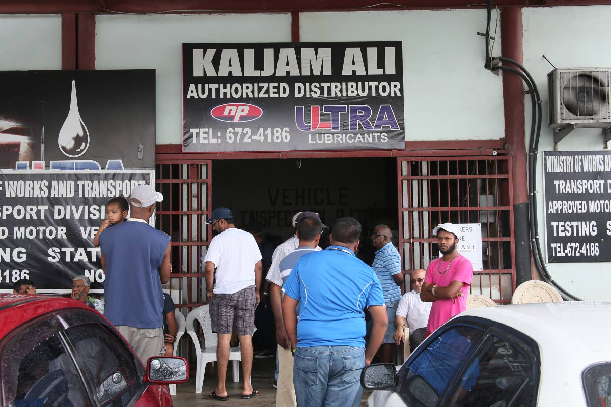 Vehicle owners stand in line to process their inspection certificates at Kajim Ali  vehicle testing station on Monroe Road, Chaguanas yesterday. PHOTO BY AZLAN MOHAMMED