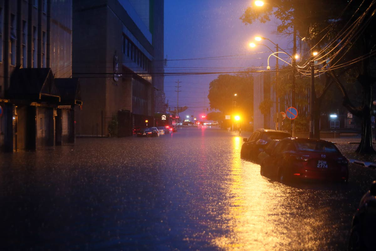 UNDER WATER: The glow of streetlights reflect on flood waters at Independence Square, Port of Spain.   PHOTO BY AZLAN MOHAMMED