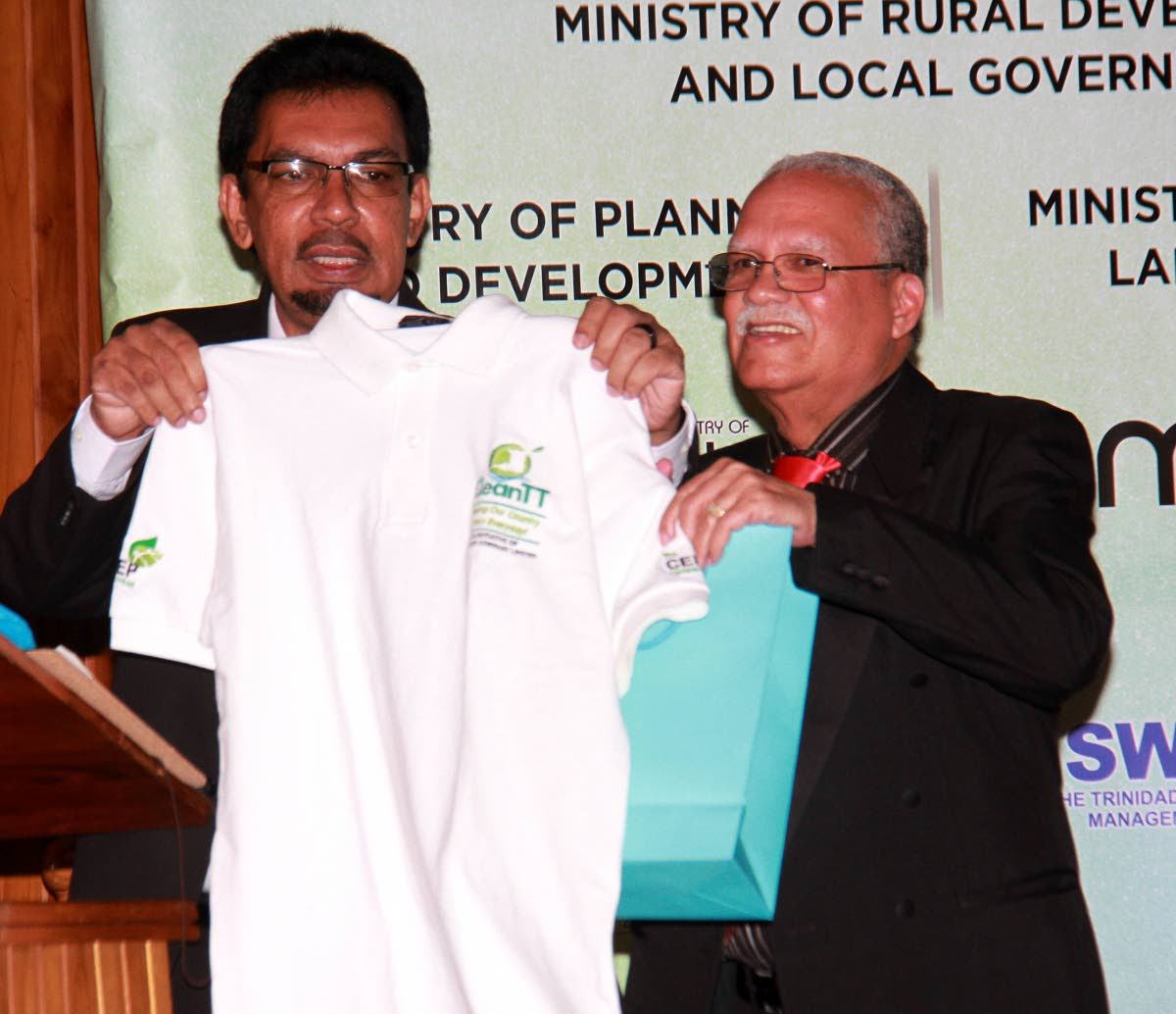 LOOK, IT'S NOT A BRIBE: Local Govt Minister Kazim Hosein, left, displays a CEPEP T-shirt given to him as a gift during the launch of CEPEP's Clean TT initiative last week in San Fernando. At right is CEPEP chairman Ashton Ford.