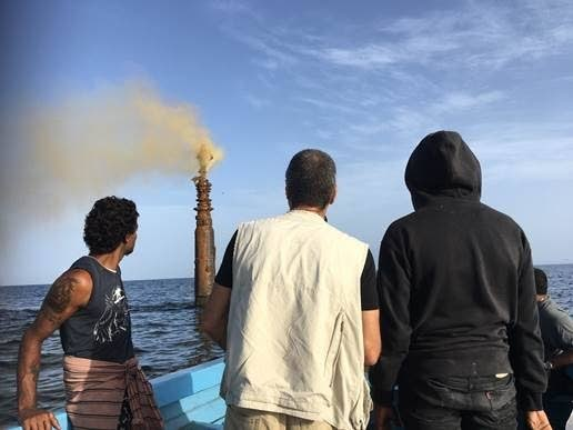 Corporate Secretary of Fisherman and Friends of the Sea (FFOS) Gary Aboud, centre, and other members of the group view the ruptured oil well at sea off Orange valley Fishing Depot in Carapichaima yesterday morning. The abandoned oil well ruptured 6 days ago.