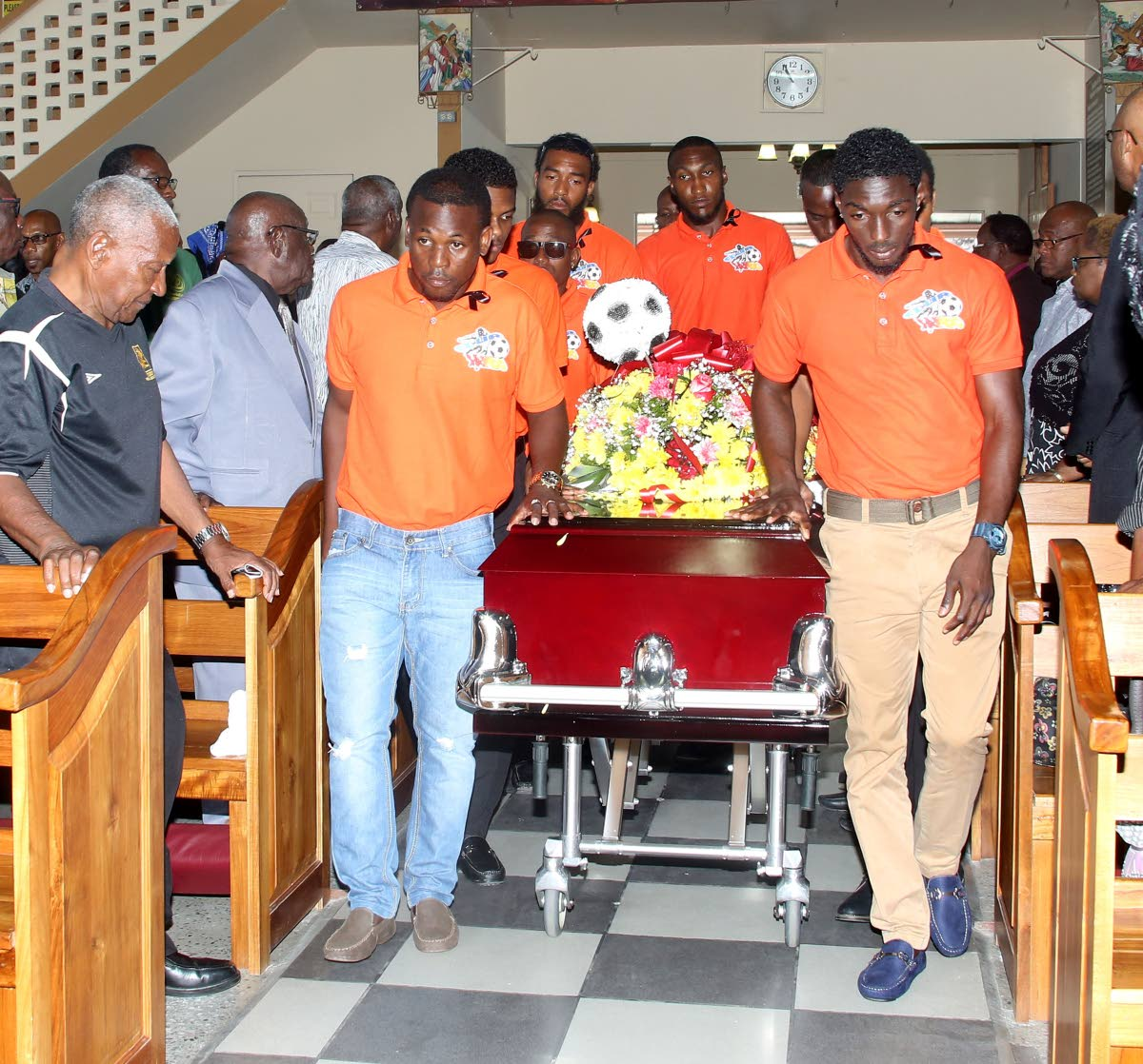 Club Sando footballers carry the casket of former TTFA director of football Muhammad Isa at his funeral at Point Fortin RC yesterday.