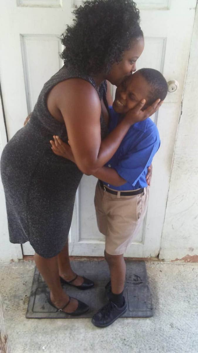 HAPPINESS: Visually impaired Jaidon Vincient, 12  is smothered  by his mother Latoya Tannis, 36. Jaidon was successful in the SEA examination  and will attend Debe Secondary school.