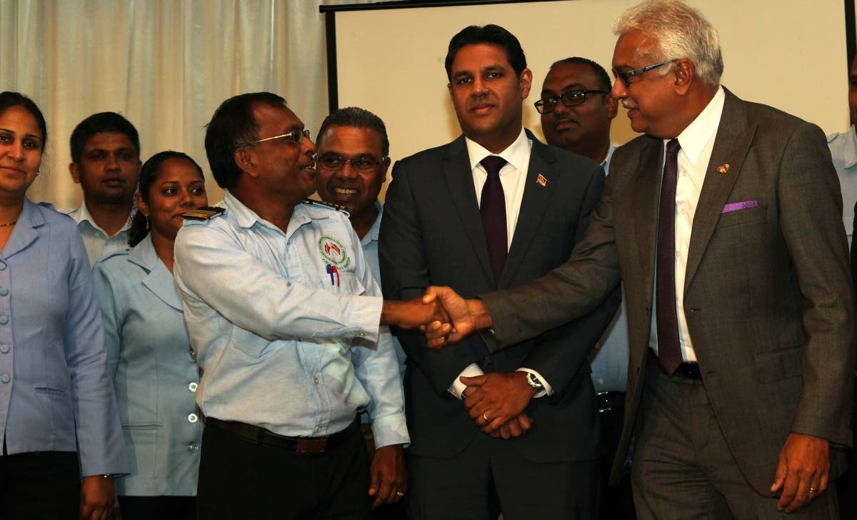 Christopher Saith, public health inspector IV, shakes the hand of Minister of Health, Terrence Deyalsingh while Chief Medical Officer Ministry of Helath, Dr Roshan Parasram look on, following the Ministry of Health Inter-Agency Media Conference on the state of readiness for the 2018 rainy season.