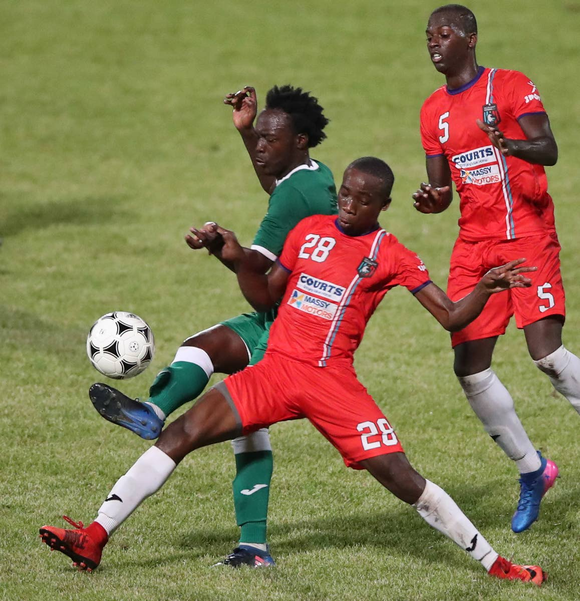 Morvant Caledonia United's Jomokie Cassimy, centre, and Joshua Sylvester, right, mark a W Connection opponent in a First Citizens Cup match at the Ato Boldon Stadium, Couva.