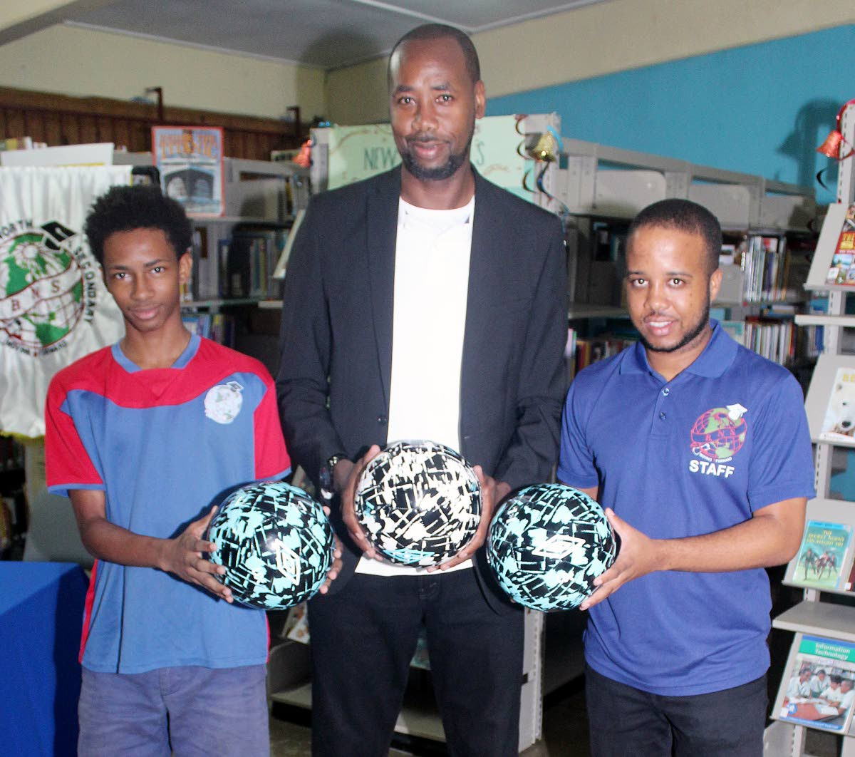 Dennis Lawrence, TT's senior men's football coach (C), Dimitri Gidaree (L), captain of Barataria North Secondary football team and Johan Redhead, the school's coach, pose with footballs donated to the school by Lawrence at the school compound in Barataria yesterday.